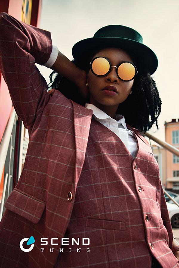 Mercedes AMG Tuning Konzept Metallic Pastell von SCEND Tuning Inspiration, eine junge Frau trägt gespiegelte Sonnenbrille 90er und einen karierten Anzug