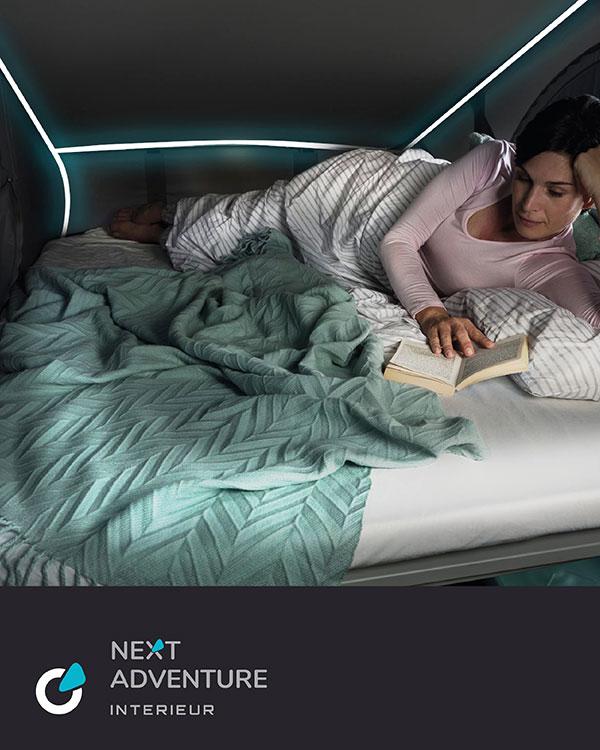 VW Volkswagen T6 Tuning Konzept von SCEND TUNING für Mutlivan und Caravan-Modelle, Ansicht Interieur mit Smart Beleuchtung, Frau liest Buch im Wohnmobil